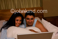 Photo of a couple propped up with pillows watching the screen of their laptop computer while laying in bed.